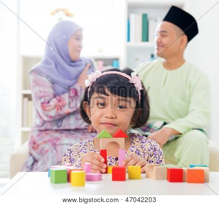 Malay girl building a wooden toy house. Southeast Asian family at home. Muslim parents and child living lifestyle.