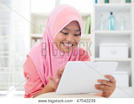 Asian teen using tablet pc computer. Southeast Asian teenager at home. Muslim teenage girl living lifestyle.