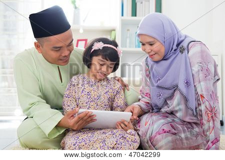 Southeast Asian family using tablet pc computer at home. Muslim family living lifestyle. Happy smiling Malay parents and child.