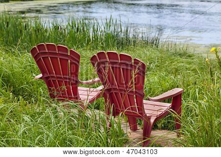 Red plastic Adirondack chairs placed for a view of the river.