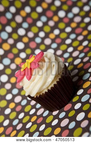 white frosted cupcake with colorful background