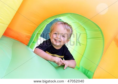 2 year old boy jumping onto an inflatable bouncy castle