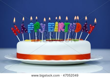 Happy birthday candles on a white cake over blue background
