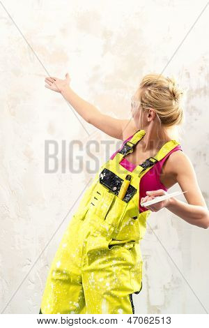 Female Construction Worker With Putty Knife Over Obsolete Background