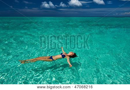 Woman in bikini lying on water at tropical beach