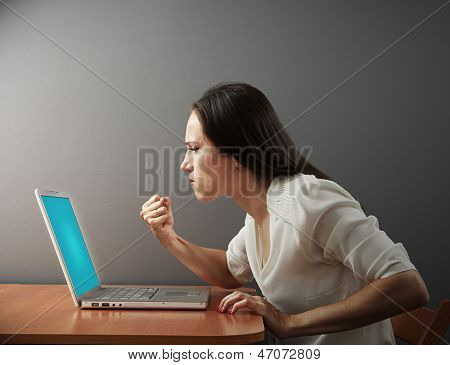 angry woman showing fist to laptop