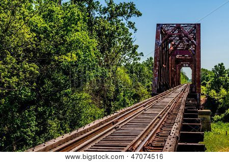 Angled View of an Old Railroad Trestle with Old Iron Truss Bridge over River.