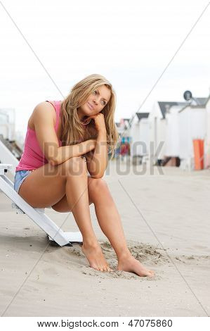 Beautiful Young Woman Sitting At The Beach With Barefeet In Sand