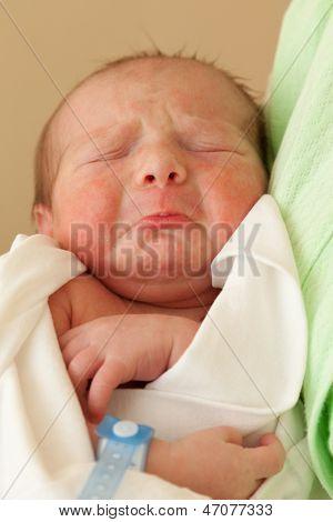 Loving mother hand holding cute sleeping newborn baby child