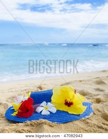 Woman's Hat With Tropical Flowers On Sandy Beach