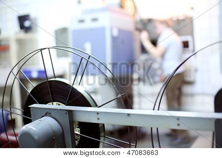 Carretes de cinta en la sala de cine y operador en el fondo. Profundidad de campo.