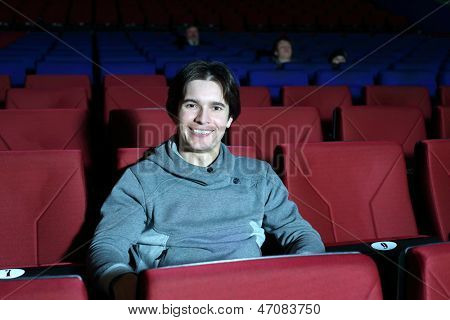 Young smiling man sits in big cinema theater and looks at camera.