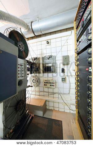 Proyector con carretes de cintas de video y equipo especial en la sala de cine.