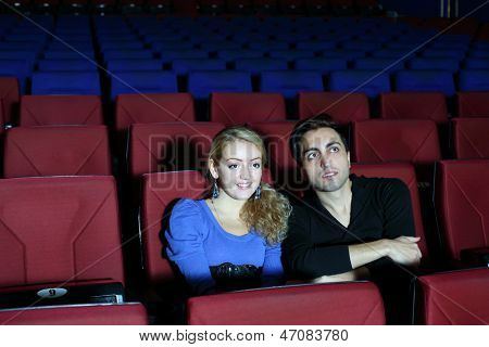 Young man and woman watch movie in movie theater. Focus on girl.