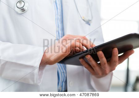 Young doctor standing in clinic reading a file or dossier on the tablet computer