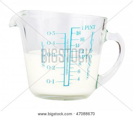 Measuring cup containing milk  isolated on white with clipping path