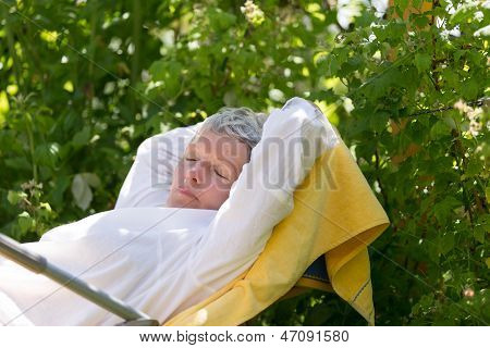 Mature Woman Sleeping On Lounger