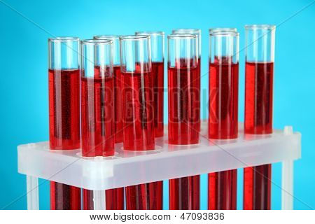 Test tubes with blood in laboratory on blue background