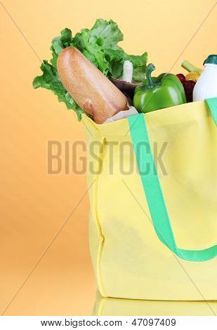 Eco bag with shopping on orange background