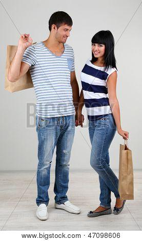 Beautiful loving couple is shopping on grey background
