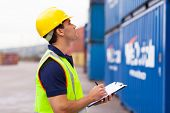 warehouse worker recording containers in shipping company
