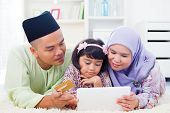 stock photo of malay  - Southeast Asian family using tablet pc computer online shopping with credit card at home - JPG