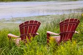 pic of bull rushes  - Red plastic Adirondack chairs placed for a view of the river - JPG