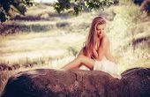 stock photo of naturist  - Beautiful nude woman lies on stones against nature background - JPG