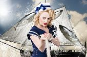 stock photo of navy anchor  - Classic retro portrait of a blond american navy pinup girl reefing in an ocean anchor with model hairstyle and definitive make - JPG