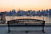 picture of bench  - Bench in park and New York City midtown Manhattan at sunset with skyline panorama view over Hudson River - JPG