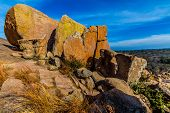 stock photo of granite dome  - Big Rocks.  Amazingly Large Granite Boulders with Yellow Lichen of the Legendary Enchanted Rock, a Small Dome Mountain, in the Texas Hill Country.