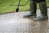 stock photo of handyman  - Outdoor floor cleaning with high pressure water jet - JPG
