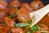 picture of meatball  - Horizontal photo of bread coated meatball in wooden spoon with basil parsley red sauce and finished meatballs in background - JPG