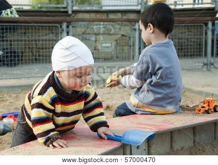 Children Playing With Sand At Playground
