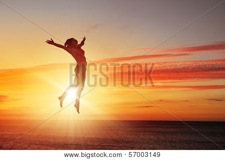 Silhouette of dancer jumping against city in lights of sunrise