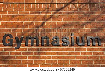 gymnasium sign on red brick