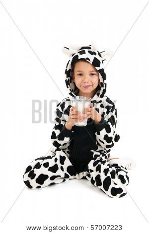 Little boy dressed as cow drinking healthy glass of milk