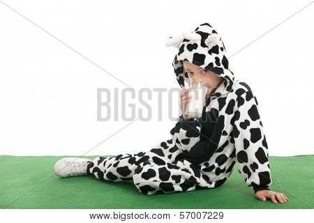 Little boy dressed as cow sitting in the grass and drinking milk