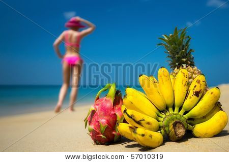 Tropical fruits and a woman in a bikini sunbathing on the beach on sea background. Idealistic scene