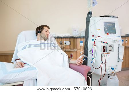 Young male patient listening to music while receiving renal dialysis in hospital room