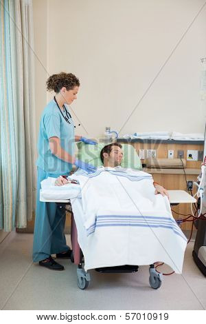 Full length of female nurse standing by patient receiving renal dialysis in hospital room