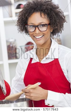 A beautiful mixed race African American girl or young woman looking happy wearing geek glasses a red apron & cooking in her kitchen at home