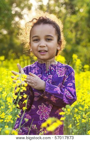 Mixed race African American female girl child backlit in a field of yellow rape seed flowers