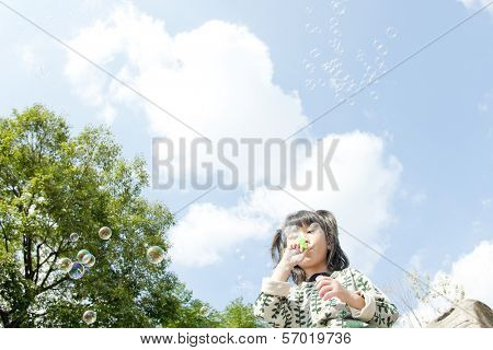 The girl who blows on soap bubbles