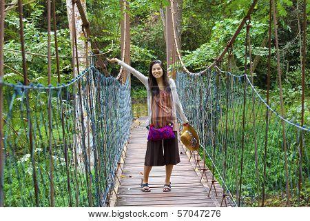 Teen Girl On Wooden Hanging Bridge In Woods