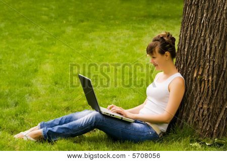 Young Woman On The Grass With Notebook