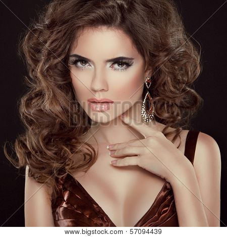Wavy Hair. Beauty Portrait Of Beautiful Brunette Woman With Long Curly Hair Poses At Dark Background