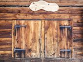 stock photo of wooden shack  - Wooden facade of a mountain hut with closed window shutters and empty plate for content - JPG