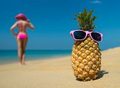 stock photo of idealistic  - Cheerful pineapple glasses and a woman in a bikini sunbathing on the beach on sea background - JPG