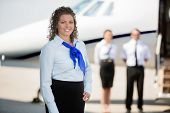 Portrait of confident airhostess smiling while pilot and colleague standing by private jet at airpor